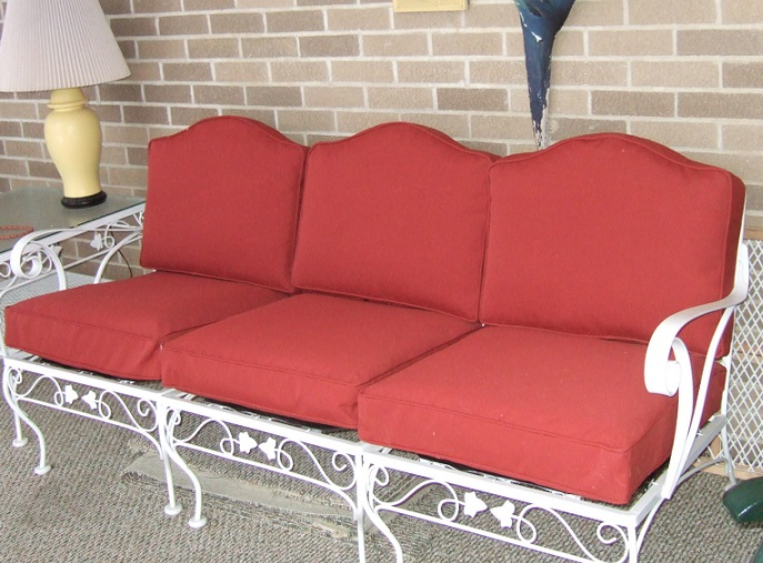 Red cushions replaced on a piece of outdoor furniture.