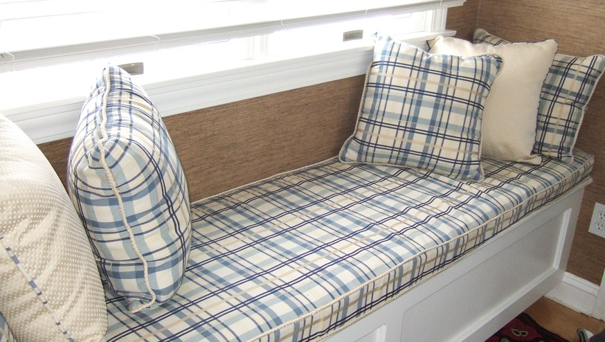 Light colored plaid window seat cushion and pillows