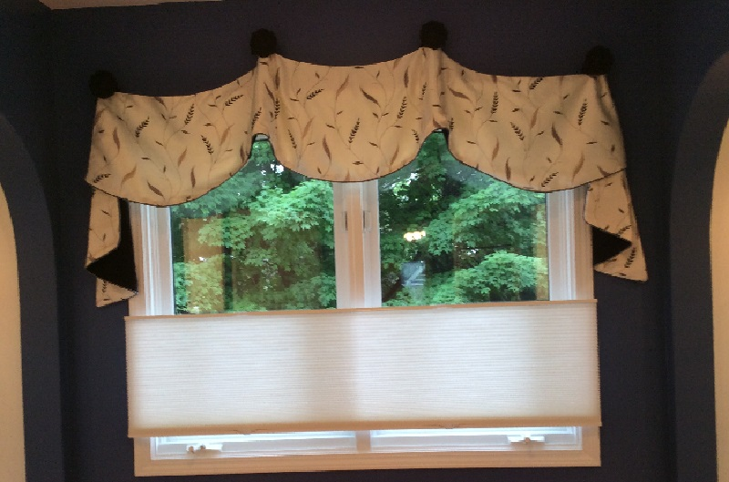 Window valance with swagger, against dark blue wall.